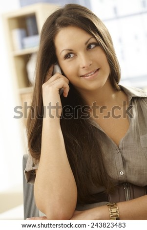 Young woman talking on mobilephone, smiling, looking away.