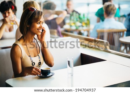 Young woman talking on the phone in coffee shop