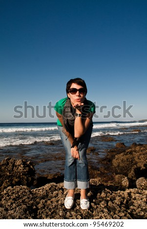 Young woman throwing kisses at the rocky coast of Lanzarote, with the sea in background