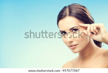 Young woman touching skin or applying cream, on blue background, with blank copyspace area for advertising slogan or text message. Caucasian female model in beauty, healthcare, skincare, face concept.