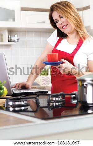 young woman using a Laptop while cooking