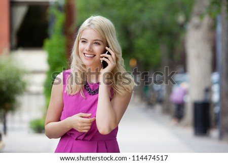 Young Woman using cell phone outdoors in city.