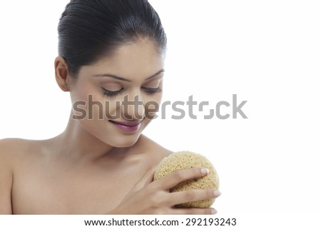 Young woman using massage sponge