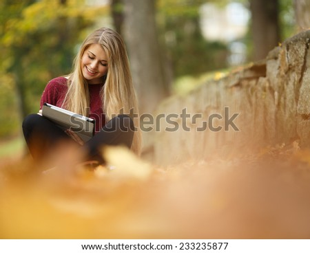 Young woman using tablet outdoor sitting on grass and smiling. Girl using digital tablet pc in the park. Student using tablet after school.