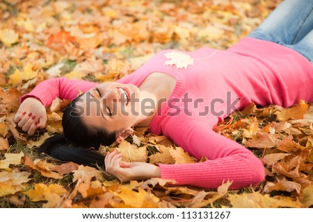 Young woman walking in the autumn park. Beauty nature scene with colorful foliage background, yellow trees and leaves at fall season. Autumn outdoor lifestyle. Happy smiling woman relax on fall leaves