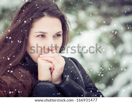 Young woman warming her hands in winter