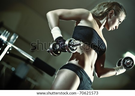 Young woman weight training. Camera angle view.