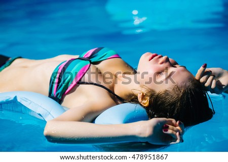 Young woman with beautiful body in colorful bikini tanning on air bed on background of blue water of pool in summer