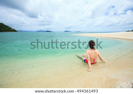 Young woman with bikini sitting in sea looking over the blue sky