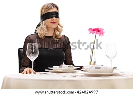 Young woman with blindfold on her eyes sitting at a romantic dinner on a blind date
