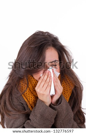 Young woman with cap sneezing in tissue, isolated on white background.
