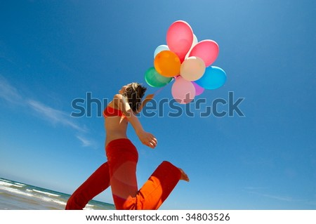 young woman with colorful balloons on the beach