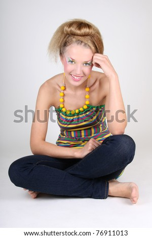 Young woman with creative make-up and coiffure sitting