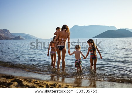 Young woman with four children walking in shallow sea waters