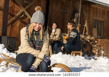 Young woman with friends enjoy weekend break snow winter cottage