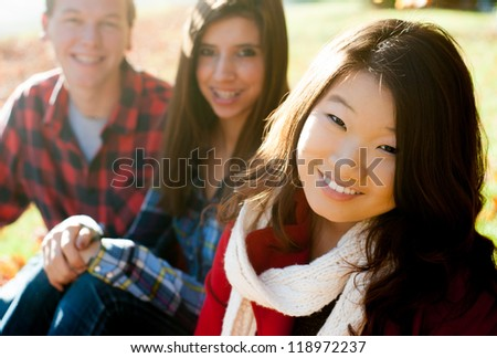 Young woman with friends in the background smiling