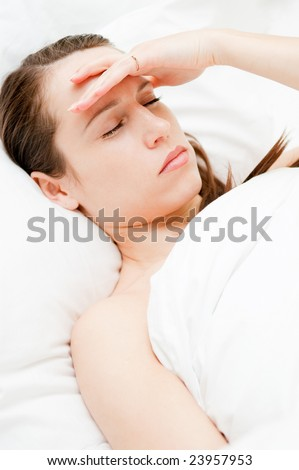 young woman with headache in her bed