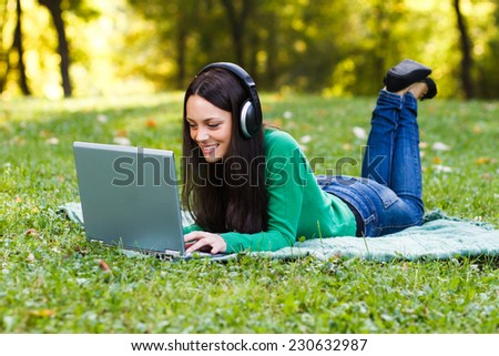 Young woman with headphones is using her laptop while lying down in the nature,Woman  with headphones using laptop