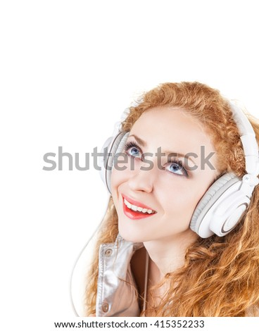 Young woman with headphones listening to music and looking up at the empty space on a white background