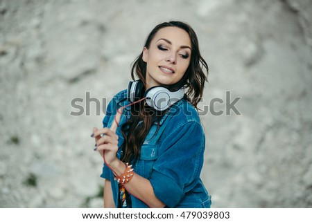 Young woman with headphones posing and dancing