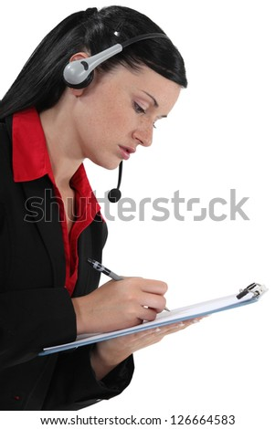 Young woman with headset and notepad