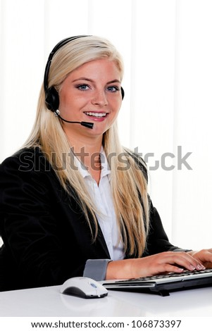 young woman with headset at computer and hotline.