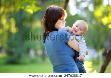 Young woman with her little baby boy at the summer park