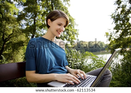 young woman with laptop in park relaxing in the sunshine