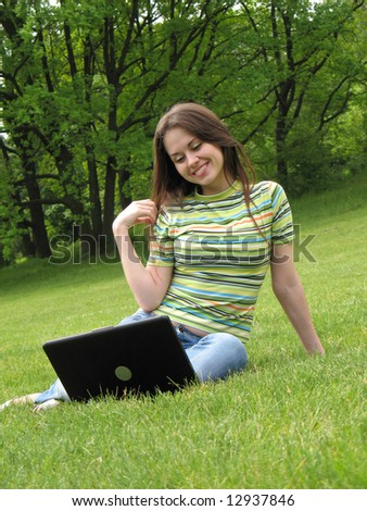 young woman with laptop on grass