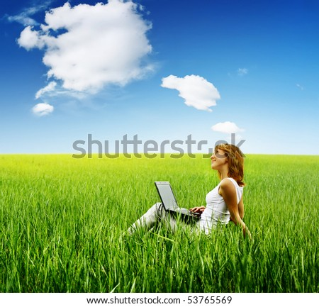 Young woman with laptop sitting on green grass under cloudy sky
