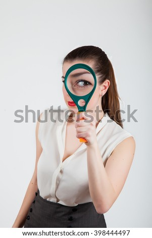 Young woman with magnifying glass on gray background