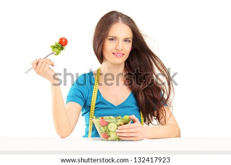 Young woman with measuring tape sitting and eating a salad isolated on white background