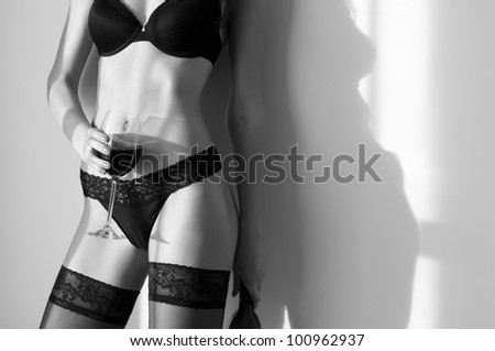 Young woman with perfect body with glass of wine