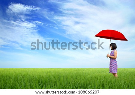 young woman with red umbrella in a green field