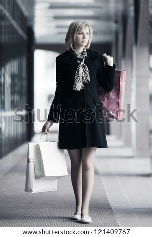 Young woman with shopping bags in a mall gallery