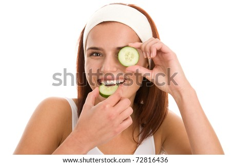 Young woman with slice of cucumber