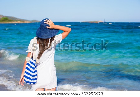 Young woman with straw hat and blue stripy bag at tropical beach