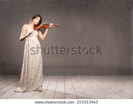 young woman with violin on gray background