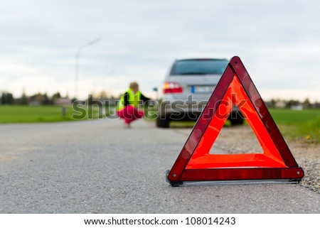 Young woman with warning triangle on street after a car breakdown