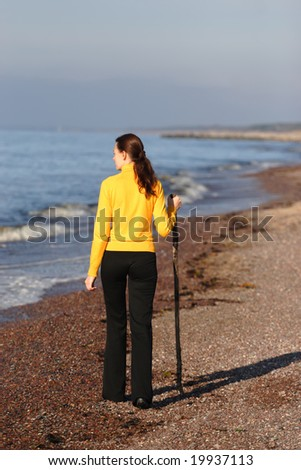 Young woman with wooden stick walking on a seaside