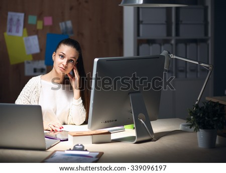 Young woman working in office, sitting at desk and talk on the phone