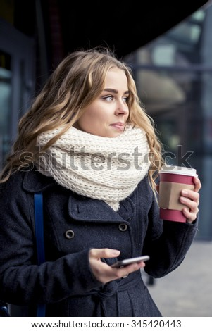 Young woman working  nearly shop. Student holding iPhone