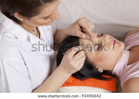 young woman working on eyelash extensions