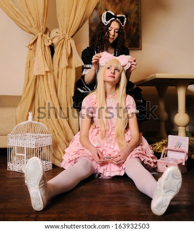 Young women dressed as dolls, sitting in the doll house.