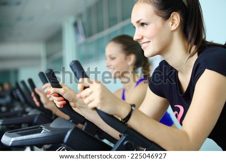 Young women exercising on stationary bicycles in fitness gym.