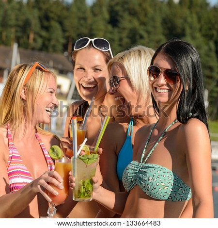 Young women in bikinis having fun with cocktails during summer