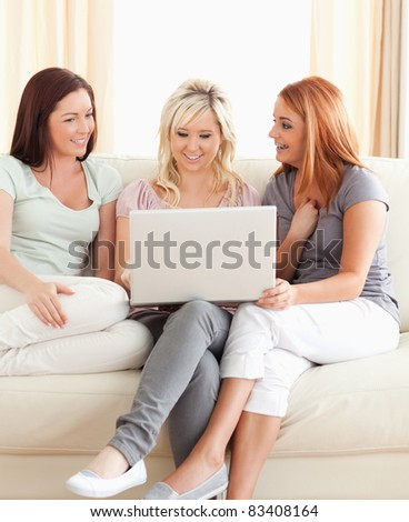 Young women lounging on a sofa with a laptop in a living room