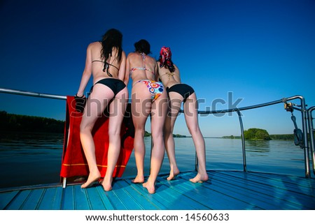 Young women models on moving boat with sexy body on a clear blue sky and copyspace