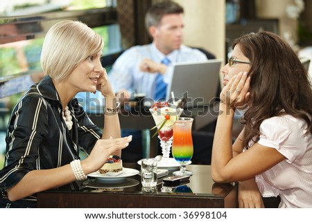 Young women sitting at coffee table in cafe having sweets, talking.