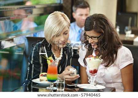 Young women sitting in cafe having sweets, looking at mobile phone.